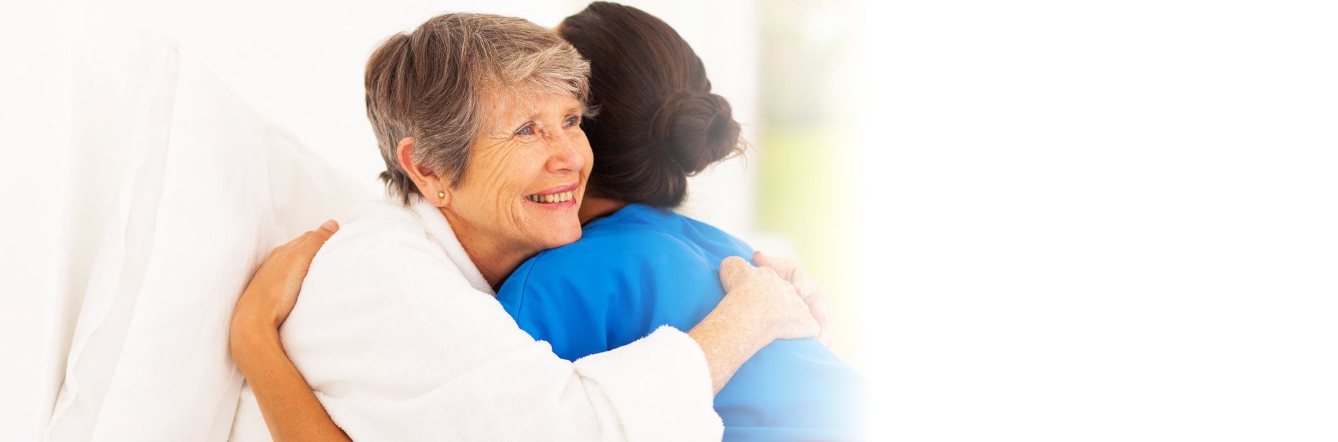 old woman and caregiver hugging each other
